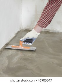 Construction worker spreading wet concrete on a floor
