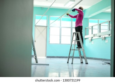 Construction worker standing on aluminium stairs or ladder using a measuring tape.