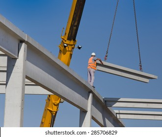 Construction worker standing on concrete beam on height and placing truss lifted by crane