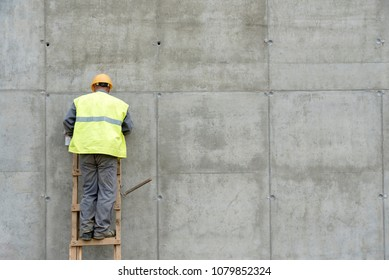 Construction worker standing on a wooden ladder dressed in yellow fixing holes in the concrete wall