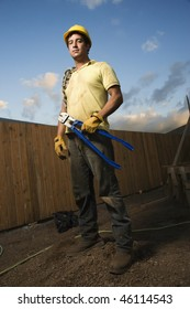 Construction worker stands on a mound of dirt while holding bolt cutters. He has a chain wrapped around his shoulder and a hardhat on. Vertical shot.