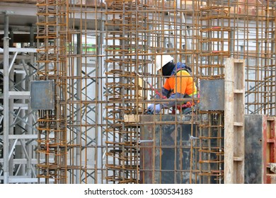 A construction worker, surrounded by re-bar, busily  wraps or ties the metal re-bar with wire.