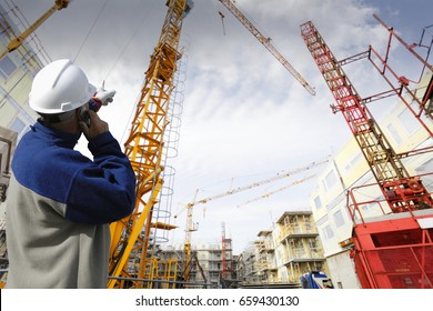 construction worker talking in phone pointing out over large building site