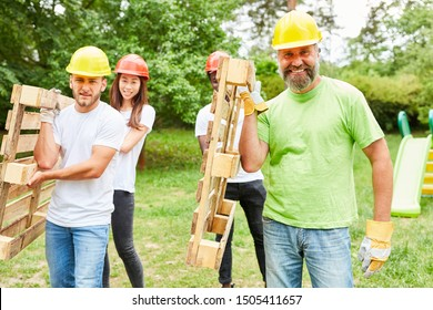 Construction worker team carries together transport pallets through a park