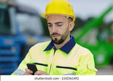construction worker texting on his phone