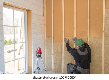 Construction worker thermally insulating eco-wood frame house with wood fiber plates and heat-isolating natural hemp material. Finishing the walls with a white wooden board, using laser line level.
