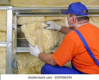 Construction worker thermally insulating house attic with mineral wool