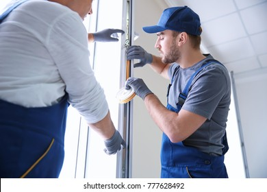 Construction worker with trainee installing window in house