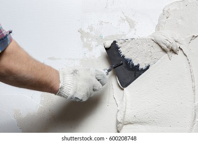 Construction worker with trowel plastering a wall