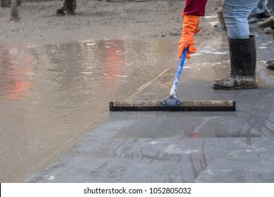 Construction worker troweling wet concrete on a top of concrete floor slab new construction site