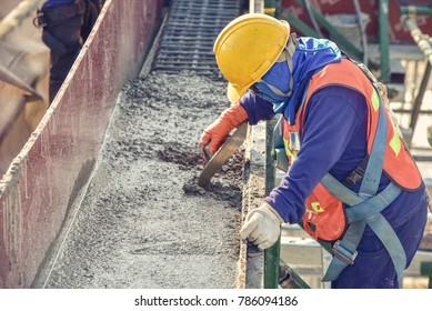 Construction worker troweling wet concrete on a top of concrete beam new construction site