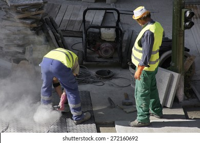 Construction worker is trying to move a kurb