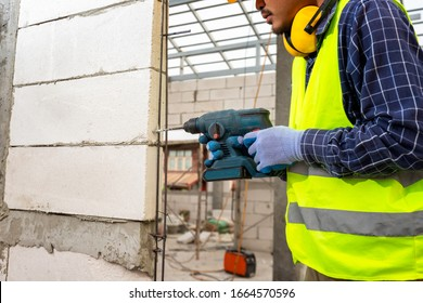 Construction worker use a drill bit,Engineer wearing safety equipment (helmet and jacket) uses a power drill to mount a aerated brick wall.