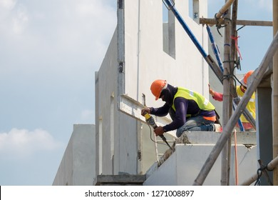 Construction worker use electric drill Drilling concrete wall in construction area, Precast house construction.