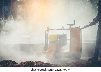 Construction worker using a concrete saw, cutting stones in a cloud of concrete dust for creating a track.