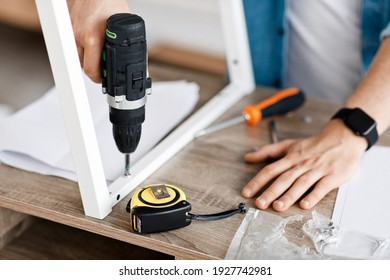 Construction worker using drill, shoots popular repair blog. Millennial man with smart watch assembles furniture with electric screwdriver and tools in interior of living room, empty space, cropped