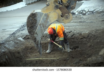 construction worker using an excavator and a shovel to repair a road drain