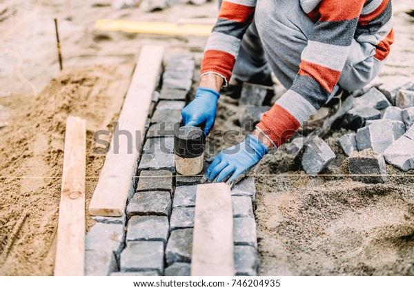 construction worker using industrial tools for stone pavement. granite blocks install details