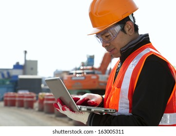 Construction worker using laptop with excavator on the background