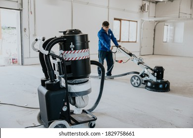 Construction worker using machine polishing surface floor smoothing and finishing hardener or epoxy concrete in the factory.