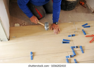 Construction worker using the rubber hammer to place a new stoneware porcelain tile floor in the home living room. Works of integral house reform