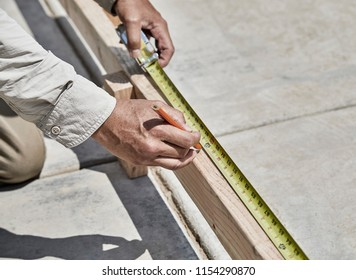 Construction worker using  tape rule to mark a measurement on a cement form board with shallow depth of field