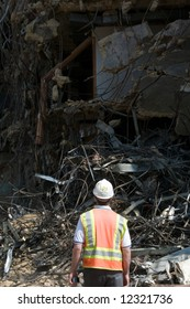construction worker wearing hard hat and safety vest stares at the wreckage of a demolition project - selective lighting for more effective copyspace