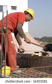 Construction worker wearing orange suit uses hammer on worksite. Vertically framed photo.