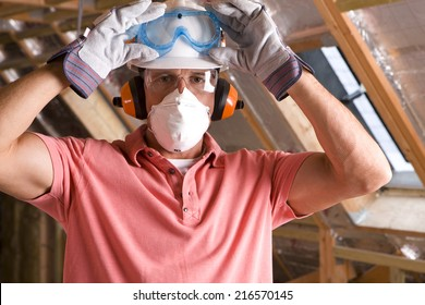 Construction worker wearing protective mask in attic