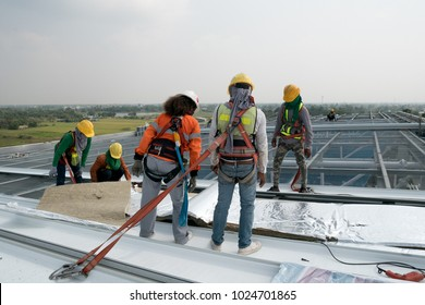 Construction worker wearing safety harness and safety line working on a metal industry roof new warehouse