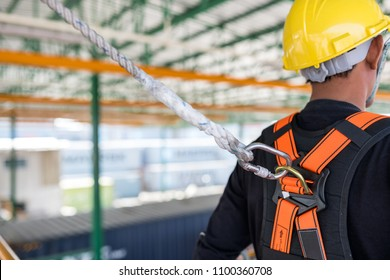 Construction worker wearing safety harness and safety line working on construction