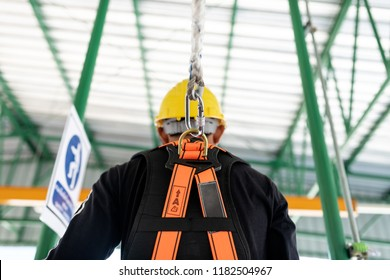 Construction worker wearing safety harness and safety line working at high place.