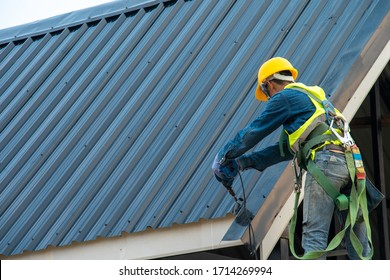 Construction worker wearing safety harness belt during working on roof structure of building on construction site,Roofer using air or pneumatic nail gun and installing metal roof tile on top new roof.