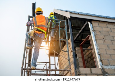 Construction worker wearing safety harness and safety line working on scaffolding at new house under construction.