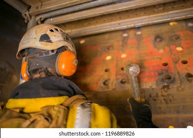 Construction worker wearing a safety orange ear muffs protection while hammering using  hammer