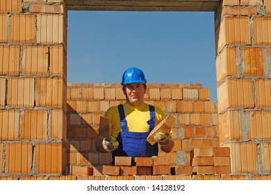Construction worker wearing yellow t-shirt and blue helmet holding stainless steel trowel and brick posing in brick wall window opening