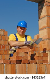 Construction worker wearing yellow t-shirt and blue helmet holding stainless steel trowel posing among unfinished brick house walls