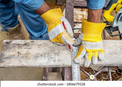 Bauarbeiter tragen Schutzhandschuhe aus Leder, mit einem Bleistift und dem Tischlerquadrat die Schnittlinie auf einem Holztisch. Bauindustrie, Hausarbeit macht es selbst.