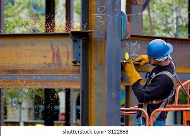A construction worker welding an iron beam