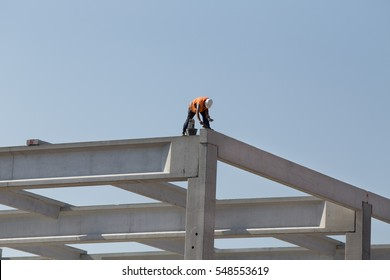 Construction worker without safety equipment working on height, fixing concrete trusses at building site