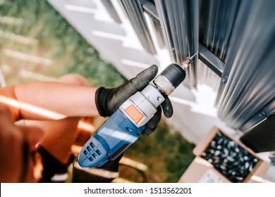 Bauarbeiter, der mit einem elektrischen Schraubenzieher auf dem Baugelände arbeitet