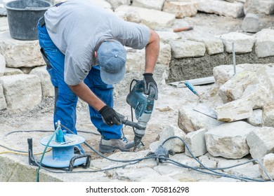 Construction worker is working with granite stones