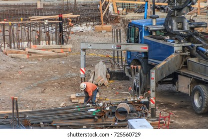 Construction worker working with iron re-bar. The worker has an orange shirt and white hard hat. There is blue truck to the right.
