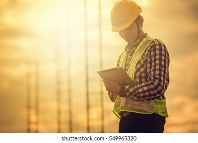 Construction worker working on site by using tablet computer.
