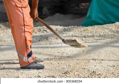 Construction worker working with shovel on new road construction