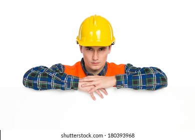 Construction worker in yellow helmet and orange waistcoat lean on a banner.  Head and shoulder studio shot isolated on white.