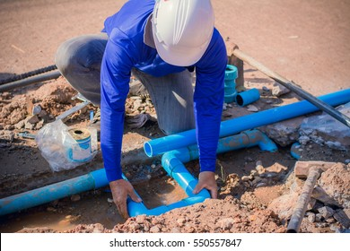 Construction worker,Repairing a broken water pipe on the concrete road.