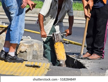 Construction workers with air hammer at the road construction