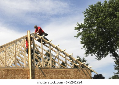 Construction workers building the roof frame of a house