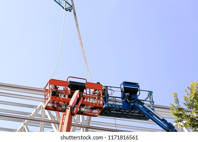construction workers in crane baskett  in roof  for maintenance,restore and repair